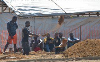 Ανθρωποι σκάβουν έναν τάφο για θύματα του Εμπολα στη Μονρόβια της Λιβερίας. Η επιδημία, που φάνηκε να υποχωρεί, απειλεί εκ νέου την Ευρώπη.