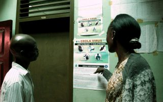 Liberian people read an information sign about Ebola set on a wall of a public health center on July 31, 2014 in Monrovia. Liberia announced on July 30 it was shutting all schools and placing