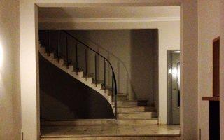 Είσοδος σε αστική πολυκατοικία της Αθήνας, στην περιοχή των Ιλισίων. Συμβολίζει μια περίοδο κοινωνικής αλλαγής στη μεταπολεμική περίοδο.