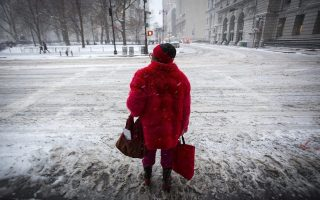 epaselect epa04587260 A woman waits to cross Centre Street near City Hall during a large winter storm in New York, New York, USA, 26 January 2015. Areas of the New York metropolitan region were expected to get up to 2 feet (60 cm) of snow.  EPA/ANDREW KELLY