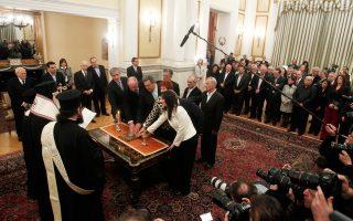 Οι ορκισθέντες κατά τον θρησκευτικό τύπο υπουργοί έχουν το χέρι τους στο Ευαγγέλιο. Τους παρακολουθούν οι συνάδελφοί τους που ετοιμάζονται για πολιτική ορκωμοσία.