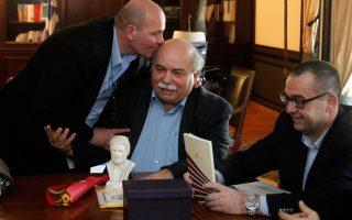 Ο Γιάννης ο Μιχελογιαννάκης  (αριστερά) ασπάζεται ευσεβώς τη φαλάκρα του Νίκου «Πόρκι» Βούτση, ο οποίος με το δεξί του χέρι προσπαθεί να αποτρέψει την ασυνήθη εκδήλωση λατρείας του ιδιόρρυθμου βουλευτή. Την ίδια στιγμή, ο γνωστός Μπαλασόπουλος της ΠΟΕ-ΟΤΑ (δεξιά), σεμνός όπως αρμόζει στην περίσταση, ρίχνει το βλέμμα του κάτω. Το κιτς της σύνθεσης ολοκληρώνει η τουριστική προτομή του αρχαίου, κλασικό δώρο που προσφέρει η ΠΟΕ-ΟΤΑ σε υπουργούς και άλλους. Πρόκειται, νομίζω, για τον Κλεισθένη, αλλά γι' αυτούς όλοι οι αρχαίοι ίδιοι είναι...