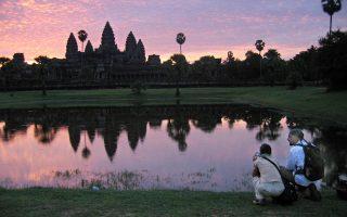 Οι ναοί του Ανγκόρ Βατ διαγράφονται στον ορίζοντα, δίνοντας την ευκαιρία στους -ενδεδυμένους- τουρίστες να τους φωτογραφίσουν.