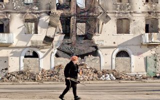 Οι εικόνες καταστροφής, όπως αυτή που αντικρίζει η ηλικιωμένη γυναίκα της φωτογραφίας στο Βουγκλερίσκ, αφθονούν στις περιοχές της ανατολικής Ουκρανίας που πλήρωσαν βαρύ τίμημα στον βωμό του εμφυλίου.