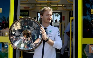 Defending Formula One Australian Grand Prix Nico Rosberg of Germany poses onboard an iconic Melbourne tram holding this year's trophy outside the famous Albert Park Grand Prix Circuit in Melbourne on March 11, 2015.    AFP PHOTO / MAL FAIRCLOUGH   -- IMAGE RESTRICTED TO EDITORIAL USE - STRICTLY NO COMMERCIAL USE