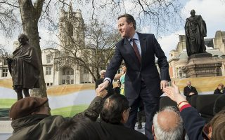 British Prime Minister David Cameron greets a crowd during a ceremony unveiling a statue of Mahatma Gandhi in Parliament square in central London on March 14, 2015. Gandhi joins figures including Britain's World War II leader Winston Churchill, who described him as a half-naked
