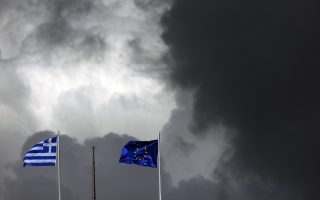 A European Union flag (R) and a Greek national flag flutter atop a building in central Athens March 28, 2015. Ratings agency Fitch on Friday cut Greece's credit rating to 'CCC' from 'B' saying lack of market access, tight liquidity and uncertainty over the timely release of aid from its official creditors are exerting pressure on government funding. REUTERS/Kostas Tsironis