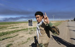 A Shi'ite fighter flashes a V-sign, near a sign painted by the Islamist State, at the town of Tal Ksaiba, near the town of al-Alam, March 7, 2015. Iraqi security forces and Shi'ite militia fighters struggled to advance on Saturday into the two towns of al-Alam and al-Dour near Tikrit, their progress slowed by fierce defence from Islamic State militants. REUTERS/Thaier Al-Sudani (IRAQ - Tags: POLITICS CIVIL UNREST CONFLICT)