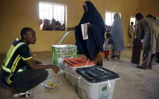 A woman cast her ballot as an elector worker eats his launch in a poling station in Kano March 28, 2015. Nigeria's electoral commission said on Saturday it would extend voting into an extra day in polling stations that had technical issues with biometric card-reading machines.    REUTERS/Goran Tomasevic
