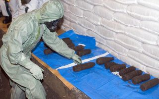A Chinese chemical weapons expert align poison gas bombs dug from a pit in Ning'an, northeastern China's Heilongjiang province, Wednesday, July 5, 2006. A joint Chinese-Japanese team was preparing Wednesday to excavate abandoned Japanese poison gas bombs from World War II that were buried near a school after a factory received them as scrap metal. (AP Photo/Ng Han Guan)