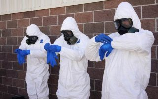 Soldiers from the U.S. Army 615th Engineer Company, 52nd Engineer Battalion, put on one of three pairs of protective gloves during the final session of personal protective equipment training at Ft. Carson in Colorado Springs, Colorado in this file photo taken October 23, 2014.  A surge of orders for gear to protect against Ebola is leading to backlogs through January for some U.S. customers, as demand expands beyond hospitals to firefighters and others, manufacturers and healthcare workers said.  REUTERS/Rick Wilking/Files  (UNITED STATES - Tags: HEALTH DISASTER MILITARY BUSINESS)