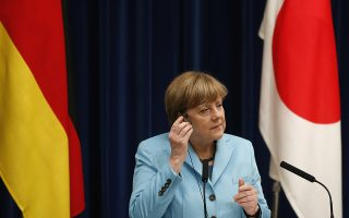 Germany's Chancellor Angela Merkel adjusts her earphone during a joint news conference with Japan's Prime Minister Shinzo Abe (not pictured) at Abe's official residence in Tokyo March 9, 2015. Merkel said on a visit to Japan on Monday that Europe faced a formidable challenge in reaching a financial aid agreement with Greece that would keep it in the euro zone. REUTERS/Toru Hanai (JAPAN - Tags: POLITICS BUSINESS)