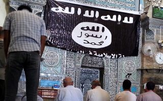epa04307452 Worshipers pray at the Al-Noori Al-Kabeer mosque, next to flag used by the Islamic State (IS), in Mosul city, northern Iraq, 09 July 2014. Abu Bakr al-Baghdadi, the leader of the Sunni extremist group Islamic State appeared for the first time on 04 July at Al-Noori Al-Kabeer mosque in Mosul city, as he was purportedly delivering the noon prayer's sermon. Fighters of IS, an al-Qaeda splinter group, have in recent weeks seized large parts of northern and western Iraq, including Mosul, and made a swift advance to capture a string of towns stretching south towards Baghdad.  EPA/STR