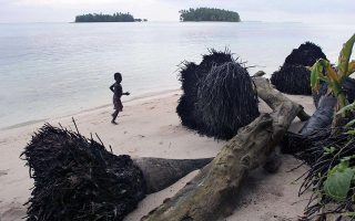 A child runs on the beach by the trunks of fallen coconut palm trees, their roots exposed by the sea erosion of the land, in Iolasa island on the Carterets Atoll, Papua New Guinea December 12, 2006. Rising sea levels have eroded much of the coastlines of the low lying Carteret islands situated 80km or 50 miles from Bougainville island, in the South Pacific. Picture taken December 12, 2006. NO ARCHIVE NO SALES REUTERS/HO/Greenpeace/Jeremy Sutton-Hibbert  (PAPUA NEW GUINEA)