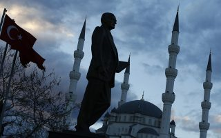A statue of modern Turkey's founder Ataturk and a mosque in the background are pictured in a square where Turkish Prime Minister Tayyip Erdogan (not pictured) is to attend an election rally of his of ruling AK Party (AKP) in Kirikkale, central Turkey March 4, 2014. Turkey will hold municipal election on March 30. REUTERS/Umit Bektas (TURKEY - Tags: POLITICS ELECTIONS)