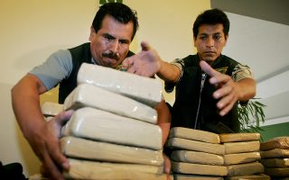 Peruvian anti-narcotic police display confiscated bricks of cocaine in Lima, February 28, 2005. Police presented 900 kilograms of cocaine value approximately in US$ 22 million, confiscated during a anti-narcotic operation on February 25, in Lima and port Callao. During the operation the police arrested 21 members of Mexico's Tijuana drug cartel including seven Mexicans and nine Colombians.       REUTERS/Mariana Bazo