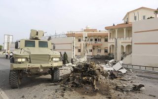 Somali government forces drive their armoured personnel carrier (APC) at the scene of a suicide car explosion in front of the SYL hotel in the capital Mogadishu January 22, 2015. The Somali Islamist group al Shabaab claimed responsibility for a bomb attack at the gate of the hotel where Turkish delegates were meeting on Thursday, a day ahead of a visit by their president, Tayyip Erdogan, to the Somali capital. REUTERS/Feisal Omar (SOMALIA - Tags: POLITICS CRIME LAW CIVIL UNREST TPX IMAGES OF THE DAY)