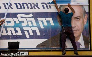 Εργάτες δήμου αφαιρούν προεκλογική γιγαντοαφίσα του νικητή της αναμέτρησης, Μπέντζαμιν Νετανιάχου, στο Ραμάτ Γκαν.