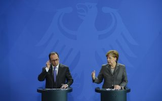 German Chancellor Angela Merkel and French President Francois Hollande (L) address a press conference on March 31, 2015 at the Chancellery in Berlin. Merkel and Hollande presided over a joint Franco-German cabinet meeting focused on defence issues.                AFP PHOTO / JOHN MACDOUGALL