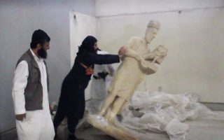 In this image made from video posted on a social media account affiliated with the Islamic State group on Thursday, Feb. 26, 2015, which has been verified and is consistent with other AP reporting, a militant topples an ancient artifact in the Ninevah Museum in Mosul, Iraq. The extremist group has destroyed a number of shrines --including Muslim holy sites -- in order to eliminate what it views as heresy. The militants are also believed to have sold ancient artifacts on the black market in order to finance their bloody campaign across the region. (AP Photo via militant social media account)
