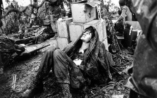 FILE - In this May 19, 1969 file photo, a wounded U.S. paratrooper grimaces in pain as he awaits medical evacuation at base camp in the A Shau Valley near the Laos border in South Vietnam on May 19, 1969 during the Vietnam War. It took nearly five years of tortuous negotiations by two U.S. administrations to hammer out the 1973 Paris Peace Accords aimed at ending the Vietnam War. The deal allowed the United States to extricate from the divisive conflict. But it had little effect for the Vietnamese, who faced two more years of war until North Vietnamese forces stormed the South Vietnamese capital of Saigon and ended the fighting on their terms - a united Vietnam under Communist rule. (AP Photo/Hugh Van Es, File)