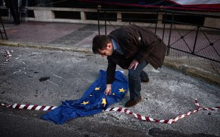 TOPSHOTSA protester picks up a disgarded European Union flag during a protest rally in Athens on April 23, 2015. European governments have come under increasing pressure to tackle the Mediterranean migrant crisis, with the last shipwreck claiming hundreds of lives on April 19, 2015. AFP PHOTO / LOUISA GOULIAMKI