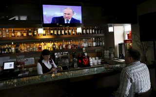 A man visits a bar during a live broadcast nationwide call-in attended by Russian President Vladimir Putin at the