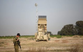 epa04001463 An Israeli soldier stands guard next to a  Iron Dome Anti-Missile Battery placed   outside the city of Ashkelon  on 26 December 2013. Tension in the region has risen in recent days on the Israel and Gaza border after an Isreli was killed allegedly by a Palestinian sniper.  EPA/ABIR SULTAN