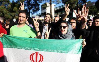 Με το σήμα της νίκης και σημαίες της χώρας τους, Ιρανοί πολίτες υποδέχονται τον υπουργό Εξωτερικών, Τζαβάντ Ζαρίφ, ο οποίος επέστρεψε στην Τεχεράνη ύστερα από την αίσια έκβαση των διαπραγματεύσεων της Λωζάννης για το ιρανικό πυρηνικό πρόγραμμα.