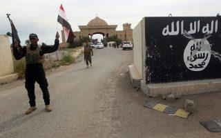 Σιίτες πολιτοφύλακες, οι οποίοι συμμετείχαν στη νικηφόρα εκστρατεία για την απελευθέρωση της Τικρίτ από το Ισλαμικό Κράτος, ποζάρουν μπροστά από τοιχογραφία με το έμβλημα των τζιχαντιστών, σε προεδρικό μέγαρο της Τικρίτ.