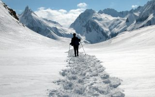 A lone mountain hiker walks in the snow as she enjoys the winter landscape of the Formazza Valley, near Riale, northern Italy, Sunday, April 11, 2004. (AP Photo/Fabio Polimeni)