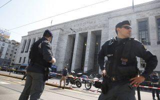 Αστυνομικοί στέκονται έξω από το δικαστικό μέγαρο του Μιλάνου μετά το βίαιο επεισόδιο που στοίχισε τη ζωή σε τρεις ανθρώπους, τη στιγμή που ένας τέταρτος υπέστη καρδιακή προσβολή από τον πανικό που προκλήθηκε.