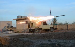 A vehicle belonging to Shi'ite fighters fires a multiple rocket launcher during clashes with the Islamic State on at the outskirt of Balad, north of Baghdad December 26, 2014. Picture taken December 26, 2014.  REUTERS/Stringer (IRAQ - Tags: CIVIL UNREST CONFLICT MILITARY)