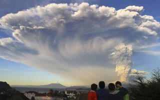 In this Wednesday, April 22, 2015 photo, children watch the Calbuco volcano erupt, from Puerto Varas, Chile. The volcano erupted billowing a huge ash cloud over a sparsely populated, mountainous area in southern Chile. Authorities ordered the evacuation of the inhabitants of the nearby town of Ensenada, along with residents of two smaller communities. (AP Photo/Carlos F. Gutierrez) - CHILE OUT - NO USAR EN PUBLICACIONES O WEBSITES EN CHILE