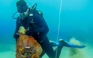 O δύτης καθαρίζει τον πυθμένα της θάλασσας από τα πλαστικά απορρίμματα (από MΓΦI).