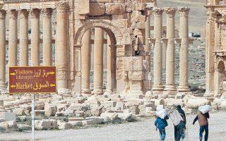 Σύροι περπατούν στην όαση της αρχαίας πόλης της Παλμύρας. Το «Ισλαμικό Κράτος» απειλεί το μνημείο παγκόσμιας κληρονομιάς της UNESCO.