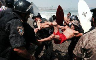 Σέρφερς εναντίον αστυνομίας. Με τα μαγιό και τις σανίδες τους οι σέρφερ της περίφημης παραλίας La Pamqilla της Λίμα στάθηκαν εμπόδιο στα σχέδια της κυβέρνησης για επέκταση του δρόμου. Οι αστυνομικοί επενέβησαν και έδιωξαν κουβαλητούς τους ημίγυμνους διαδηλωτές για να προχωρήσουν οι μπουλντόζες στο μπάζωμα της παραλίας που είναι φημισμένη παγκοσμίως για τα μεγάλα κύματά της.  AFP PHOTO/RENZO GIRALDO