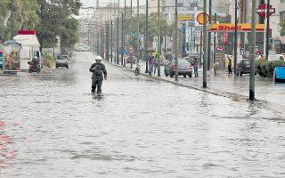 Πεζός προσπαθεί να διασχίσει την οδό Πειραιώς, που έχει πλημμυρίσει από την έντονη βροχόπτωση. Από τις 3-4 μ.μ. διεκόπη χθες η κυκλοφορία στην οδό, μεταξύ Πέτρου Ράλλη και Χαμοστέρνας, αλλά και σε άλλους κεντρικούς δρόμους της Αθήνας, προκαλώντας σοβαρά μποτιλιαρίσματα και χάος.