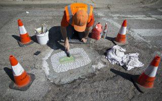 Μετά τα γκράφιτι στους τοίχους, τα ψηφιδωτά στις λακκούβες. Ο καλλιτέχνης Jim Bachor τρίβει τα υπολείμματα τσιμέντου πάνω από το έργο του με τίτλο «Twin Lime Popsicles». Εδώ και καιρό οι λακκούβες στους δρόμους του Σικάγου γεμίζουν με τσιμέντο και έργα που απεικονίζουν μπουκέτα από λουλούδια, λέξεις που γράφουν «Λακκούβα» και παγωτά, όλα φτιαγμένα από ψηφίδες μαρμάρου και γυαλιού, σε ένα πρωτότυπο τρόπο προσέγγισης του κοινού και διάθεσης της τέχνης. REUTERS/Jim Young