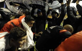 Argentina's River Plate footballers leave the pitch under police shields after the match was suspend before start the second time of the Copa Libertadores 2015 round before the quarterfinals second leg football match against Argentina's Boca Juniors at the