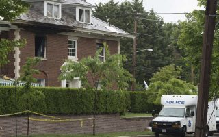 Police vehicles are seen outside a fire-damaged home where four people were killed last week in Washington, DC, May 21, 2015. Police were on the hunt Thursday for a suspect in the murder of a wealthy Washington family, after he was reportedly identified using DNA collected from the crust of a pizza delivered to victims' home. Authorities have issued an arrest warrant for Daron Dylon Wint in connection with the four murders, one of the most notorious crimes in recent memory in the US capital city. The victims -- Savvas Savopoulos, president and CEO of American Iron Works, a building materials manufacturer in Maryland, his wife Amy, their 10-year-old son Philip and the family's housekeeper Veralicia Figueroa -- were found bound and bludgeoned May 14 after a fire gutted the millionaire's mansion in an exclusive section of Washington.  AFP PHOTO / SAUL LOEB
