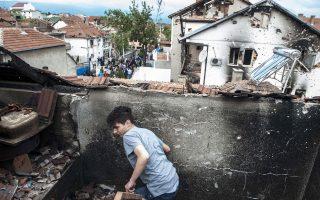 Ενα αγόρι περπατάει ανάμεσα στα απομεινάρια κατεστραμμένου σπιτιού στο Κουμάνοβο, στην ΠΓΔΜ, μετά τα αιματηρά επεισόδια.