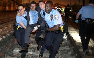 Τραυματιοφορείς βοηθούν έναν επιβάτη στο σημείο του τραγικού δυστυχήματος.