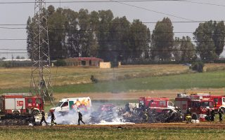 Emergency services personnel work at the scene after a plane crash near the Seville airport, in Spain, Saturday, May 9, 2015. A military transport plane crashed near southwestern Seville airport Saturday, killing its crew, Spain's prime minister said. It is unclear if any others were injured. Mariano Rajoy said up to 10 crew members were aboard the brand new Airbus A400M aircraft that was undergoing flight trials at the airport. (AP Photo/Miguel Angel Morenatti)
