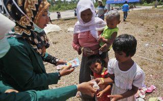Μαθητές στο Ατσεχ της Ινδονησίας προσφέρουν τρόφιμα στα παιδιά των Ροχίνγκια, σε προσωρινό καταφύγιο.
