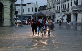 Residents cross a flooded street in downtown Havana Wednesday, April 29, 2015. Cuban officials say an intense storm has killed at least two people and caused extensive damage in the country's capital. The storm turned streets into rivers and knocked down power lines, leaving many without electricity. (AP Photo/Desmond Boylan)