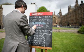 Υπάλληλος γραφείου στοιχημάτων γράφει σε πίνακα έξω από το Κοινοβούλιο τις αποδόσεις για κάθε πιθανό σενάριο («περισσότερες έδρες για Συντηρητικούς, Εργατικούς» κ.λπ.) που θα μπορούσε να προκύψει από τις σημερινές εκλογές στο Ηνωμένο Βασίλειο.