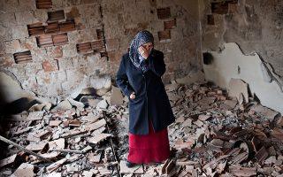 Κάτοικος του Κουμάνοβο μέσα στο κατεστραμμένο σπίτι της, μετά τα πρόσφατα επεισόδια.
