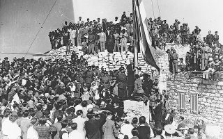 Ο πρωθυπουργός Γεώργιος Παπανδρέου υψώνει την ελληνική σημαία στην Ακρόπολη αμέσως μετά την έλευση της κυβέρνησης στην ελεύθερη Αθήνα, 18 Οκτωβρίου 1944.