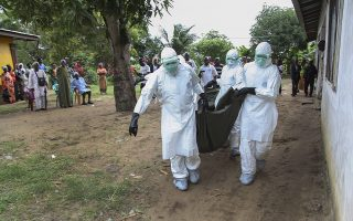 epa04343451 Liberian nurses carry the body of an Ebola victim from a home in the Banjor Community on the outskirts of Monrovia, Liberia 06 August 2014. According to statistics from the United Nations over 900 people have died from the Ebola outbreak making it the worst ever in history.  EPA/AHMED JALLANZO